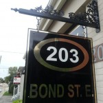 Fancy iron scrollwork completes look of this distinguished black aluminum sign